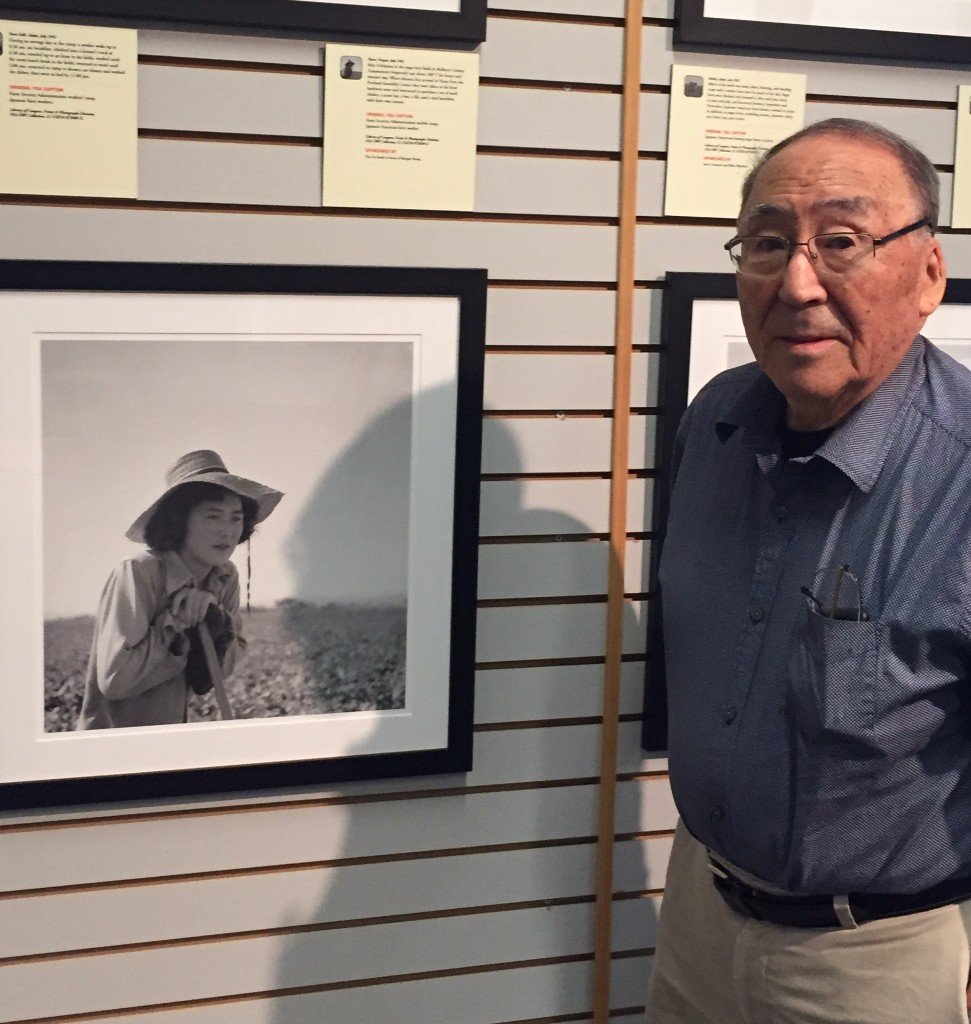 Mathias Uchiyama poses with a portrait of his sister May. Image courtesy of Susan Nagai.